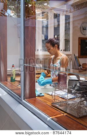young beautiful woman washing dishes cleaning kitchen at home