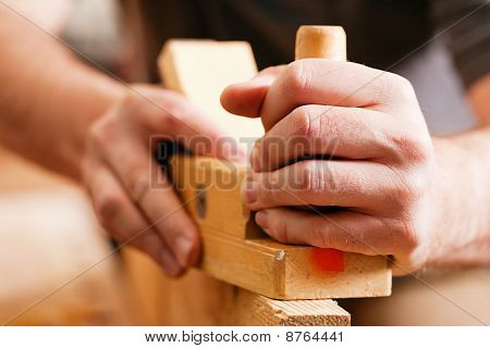 Carpenter with wood planer