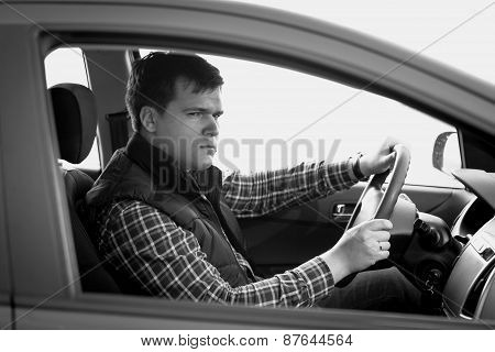 Black And White Portrait Of Concentrated Man Driving A Car