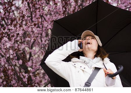 Woman With Hat And Umbrella Talking On The Phone In Spring