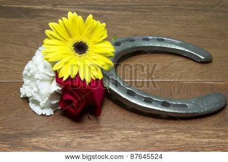 Horseshoe On Wood With Three Flowers Of The Triple Crown