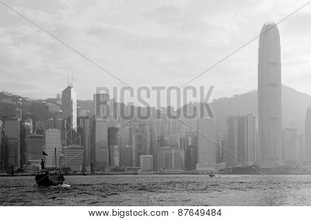 Hong Kong skyline with boats in Victoria Harbor in black and white.