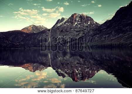 Snow mountain cloud and lake with reflections in Yosemite.