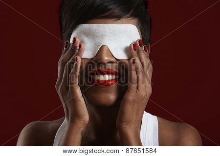Woman With Eye Mask On A Red Back