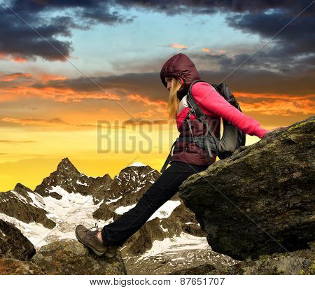 Girl sitting on rock, in the background mount Ober Gabelhorn at sunset Swiss Alps, Europe