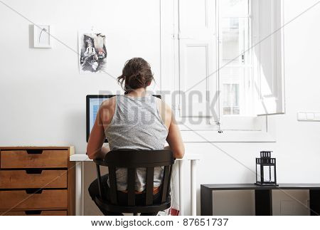 Young Man Is Working. Backside View,  Cosy Apartment