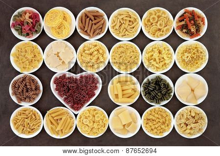 Pasta dried food selection in white porcelain bowls over lokta paper background..