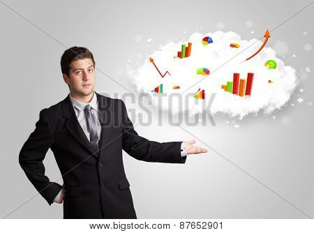 Young man presenting cloud with graphs and charts concept