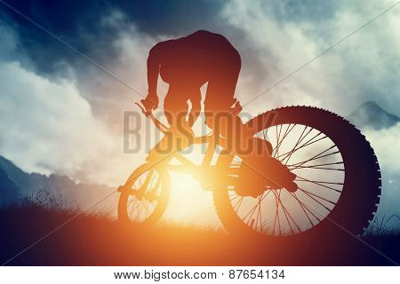 Man riding a bike in high mountains at sunset. Extreme sport, speed, risk.