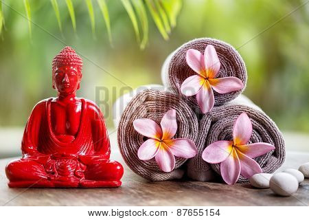 Buddha and flower in towels, wellness background