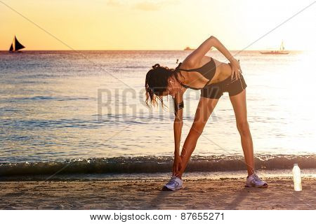 healthy lifestyle beautiful woman stretching before running at sunrise seaside