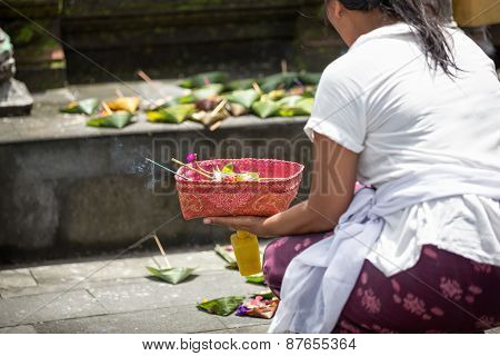 Local woman carrying offering to local temple in Bali, Indonesia. Offering flowers and other gifts is very popular tradition on Bali.