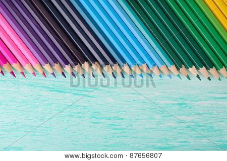 Colorful pencils on wooden table