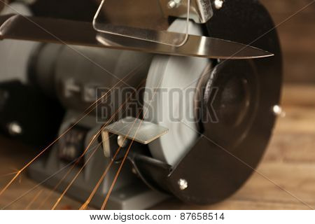 Knife sharpener on wooden table, closeup