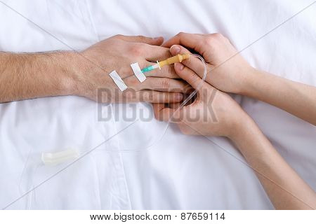 Female hands holding man hand with dropper needle on bed close-up