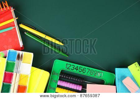 Bright school supplies on blackboard background