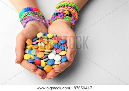 Female hands with bracelets and pile of colorful candies isolated on white