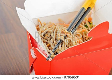 Meat and noodles in red take away container