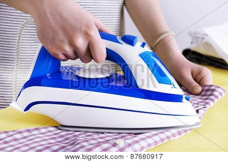 Woman ironing clothes on ironing board, closeup