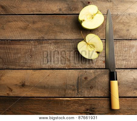 Sliced apple with knife on wooden background