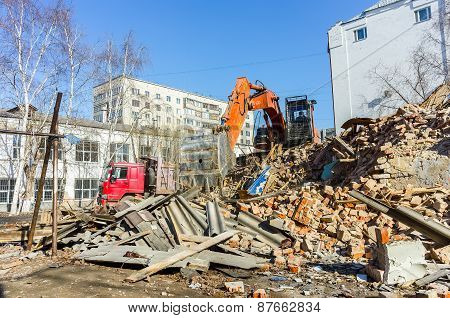 Excavator works garbage from demolished house