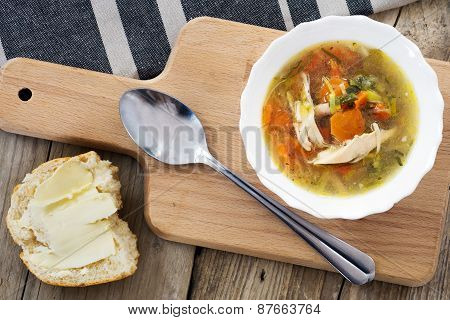 Chicken Broth With Vegetables And A Half Bun On A Wooden Board