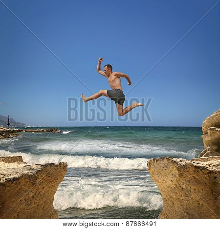 Man Jumping Over The Abyss Between Two Rocky Mountains.