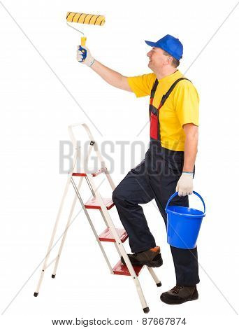Worker on ladder with roller and bucket.