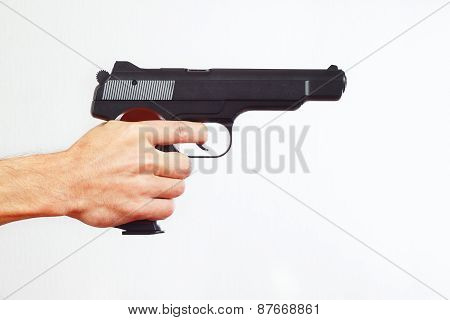 Hand with semi-automatic gun on white background