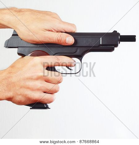 Hands reload handgun on white background