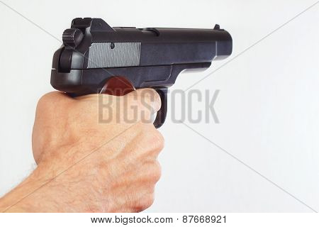 Hand with semi-automatic handgun closeup