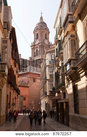 MALAGA, SPAIN - MAR 14 2015 : Visitors and residents wander down the streets beneath the cathedral.