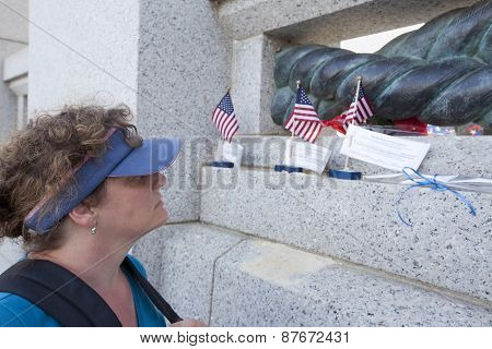 Woman Looking At Memorial For Fallen Veteran,