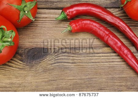 Two Fresh Red Hot Chili Peppers And Tomatoes