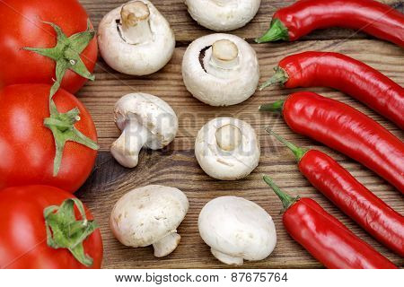 Chili Peppers, Fresh Tomatoes And  Mushrooms On Wooden Board
