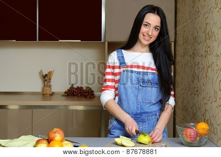 Brunette Housewife In Blue Overalls Cuts An Apple In The Kitchen.