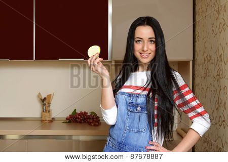 Brunette Housewife In Blue Overalls Holding A Piece Of Apple And Smiling.