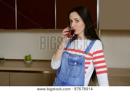 Brunette Housewife In Blue Overalls Drinks Juice From A Glass Beaker.