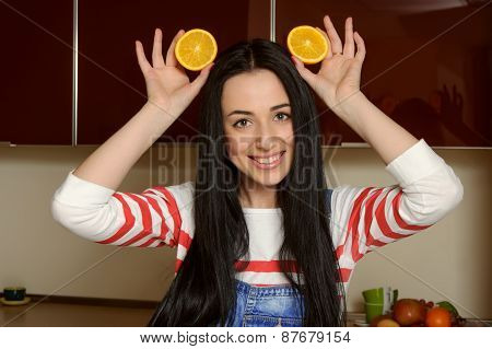 Housewife Holding Orange Slices Over Her Head And Laughs