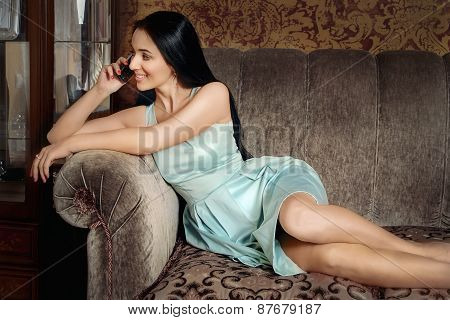 Beautiful Girl Lying On The Couch And Speaks By Phone