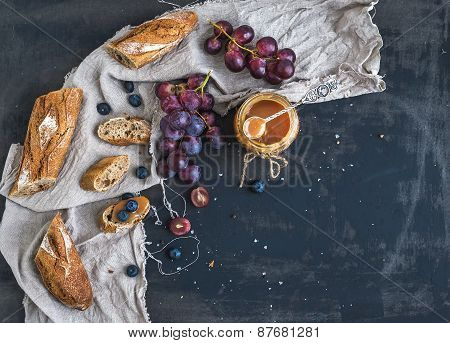 French Baguette Cut Into Pieces, Red Grapes, Blueberry And Salt Caramel Sauce On Rustic Dark Backgro
