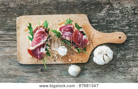 Brushetta Set With Smoked Meat, Arugula, Garlic And Dried Tomato
