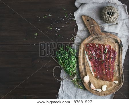Cured Pork Meat Prosciutto On A Rustic Woodem Board With Garli