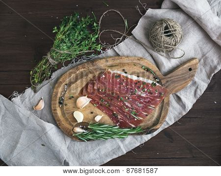 Cured Pork Meat Or Prosciutto On A Rustic Woodem Board With Garli