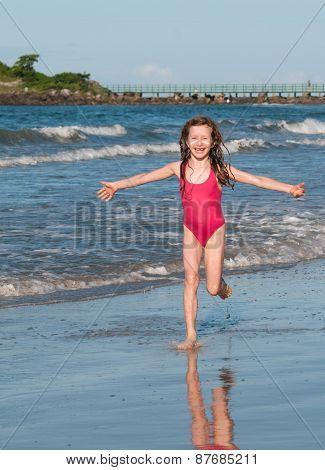 Girl running on the beach sand.