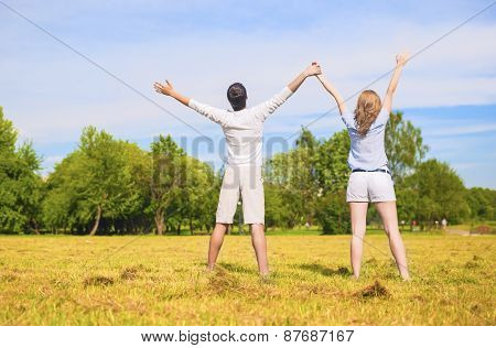 Young Caucasian Couple Standing Together On Grass Meadow With Hands Lifted Up