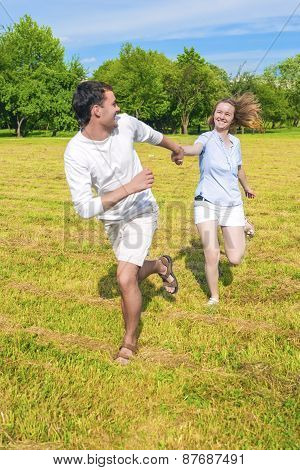 Smiling Caucasian Couple Relaxing Outdoors And Having Fun Together. Running On Grass Meadow With Han