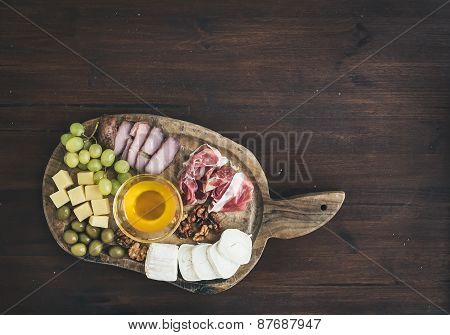 Wine Appetizers Set: Meat And Cheese Selection, Honey, Grapes, Walnuts And Olives On A Rustic Wooden
