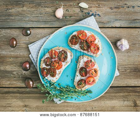 Rustic Breakfast Set Of Sandwiches With Soft Cream-cheese, Cherry-tomatoes Roasted With Garlic
