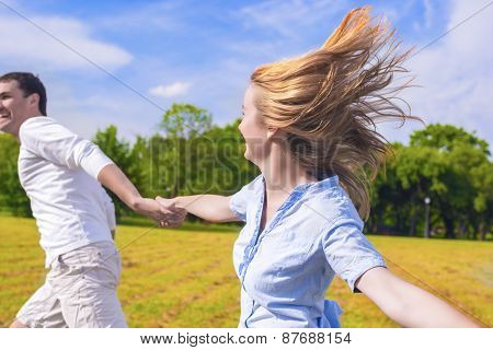 Youth Lifestyle: Caucasian Couple Relaxing Outdoors. Man Dragging Her Lady By Hands.  Holiday And Va